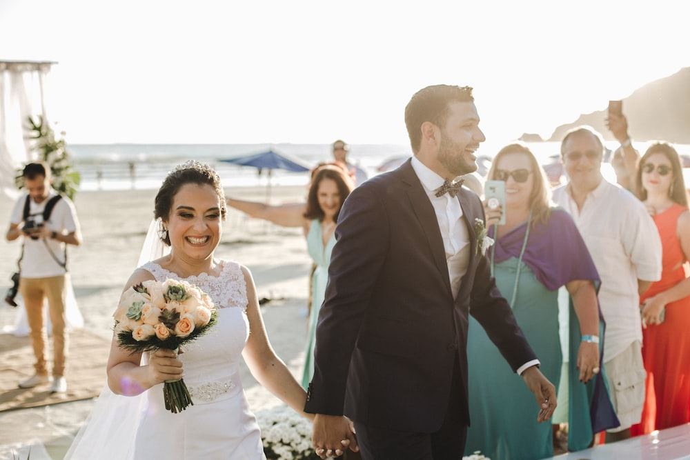 smiling man and woman in wedding dress and suit