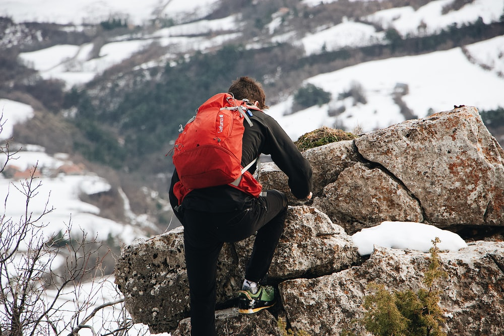 man climbing up rocks in a snowy mountain