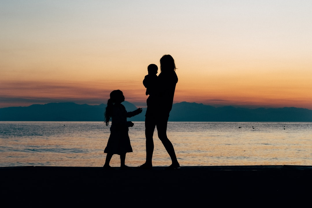 A family of three. Brother, sister and mother, stroll on the beach in Greece at sunrise. When the kids can't sleep on holiday, take them for a walk on the beach. If you can wake up it makes great photos for the golden hour.