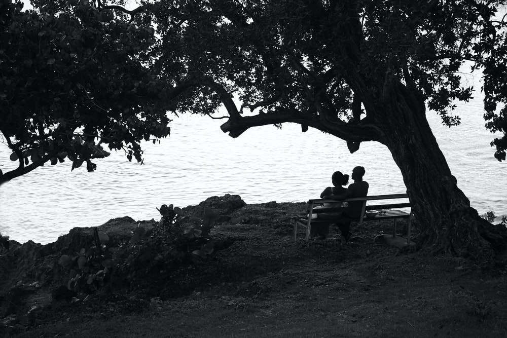 grayscale photography of couple sitting on bench