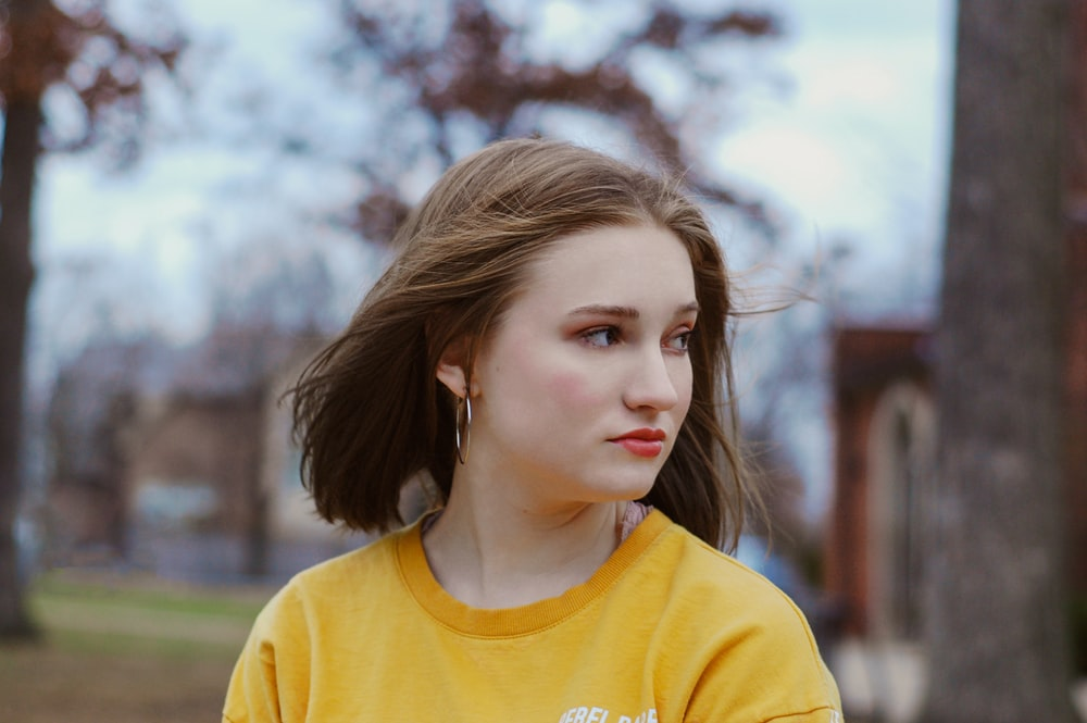 selective focus photography of woman wearing yellow crew-neck shirt