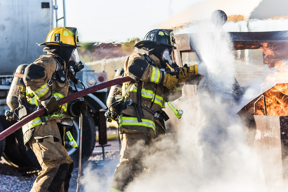 three fireman preventing fire during daytime