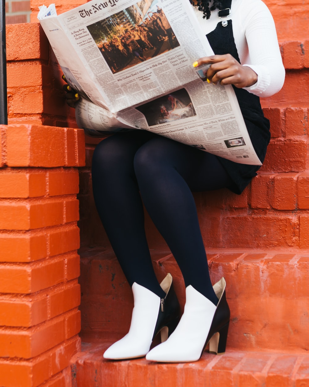 woman sitting on concrete stairs while reading newspaper