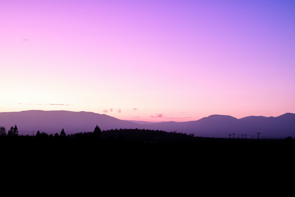 silhouette photography of land under a purple sky during daytime