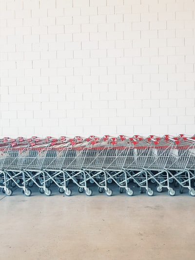 gray-and-red metal shopping cart lot beside wall