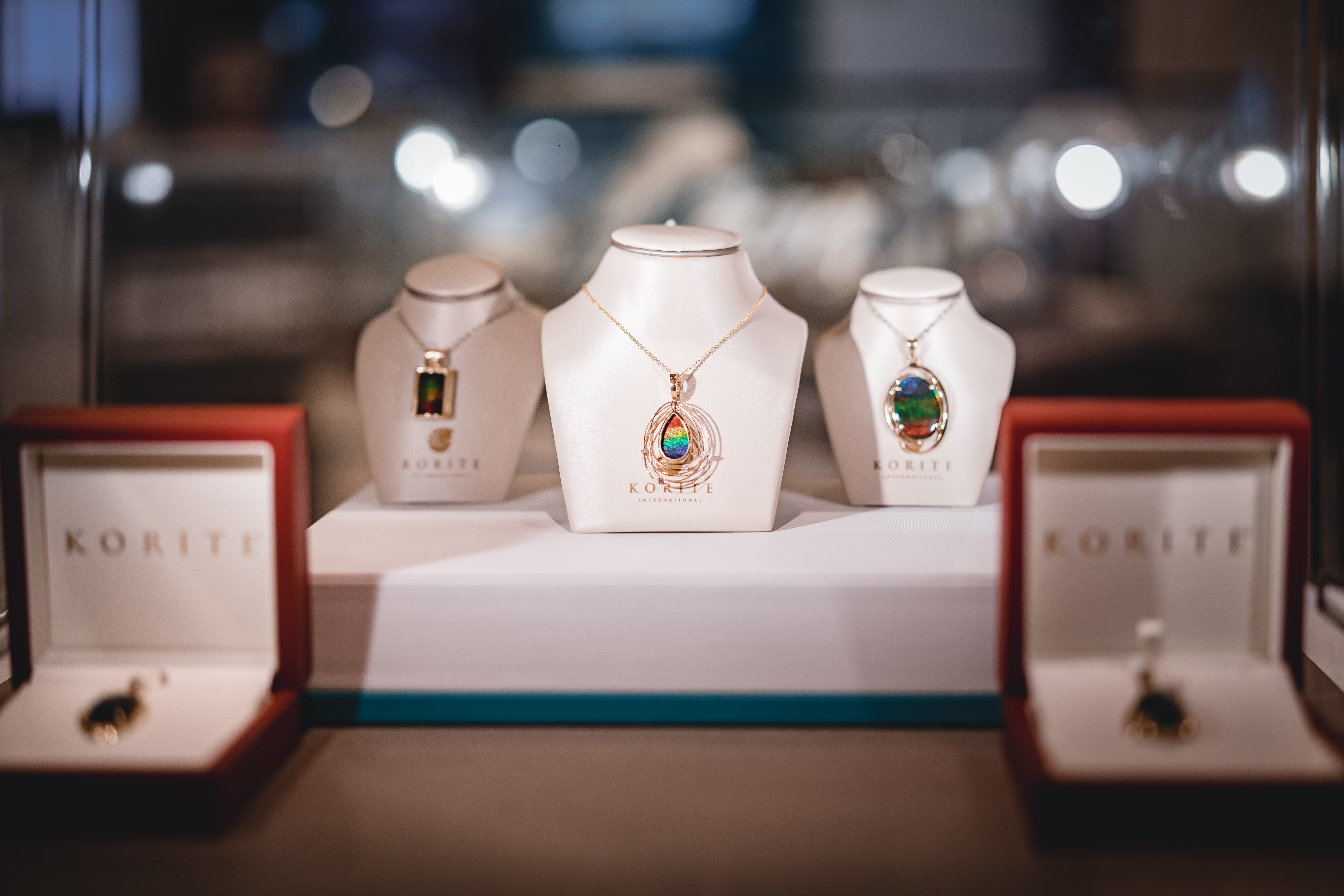 several assorted-color necklaces with pendants and boxes