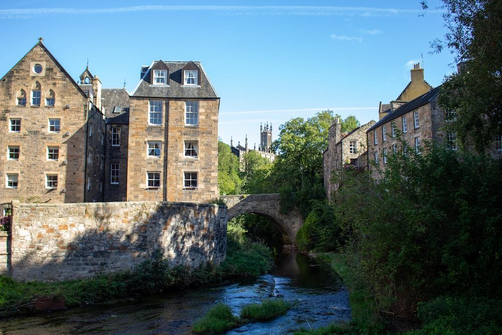 stone houses beside a canal under a calm blue sky