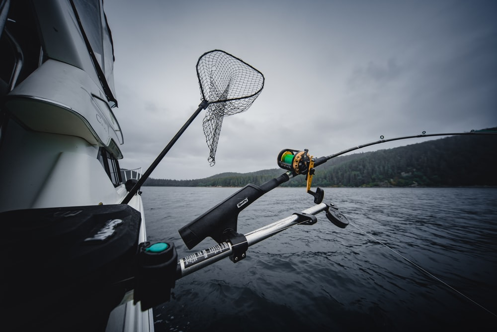 fishing rod and net hanging from a boat in the sea