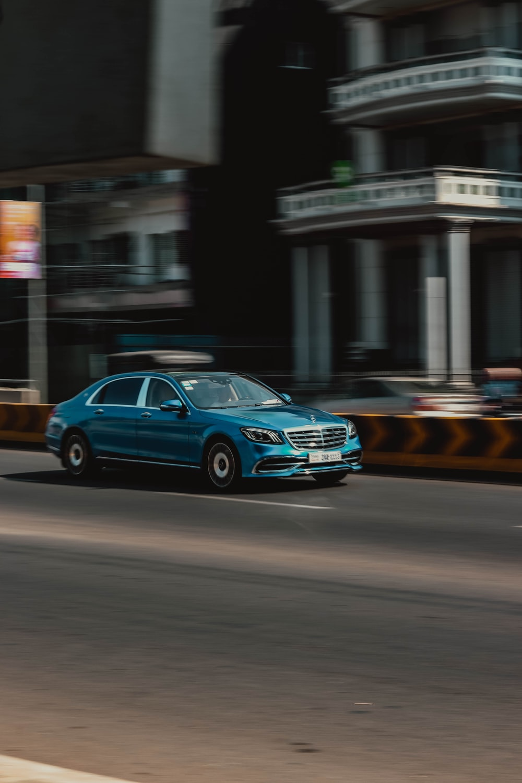 panning photography of blue sedan on road