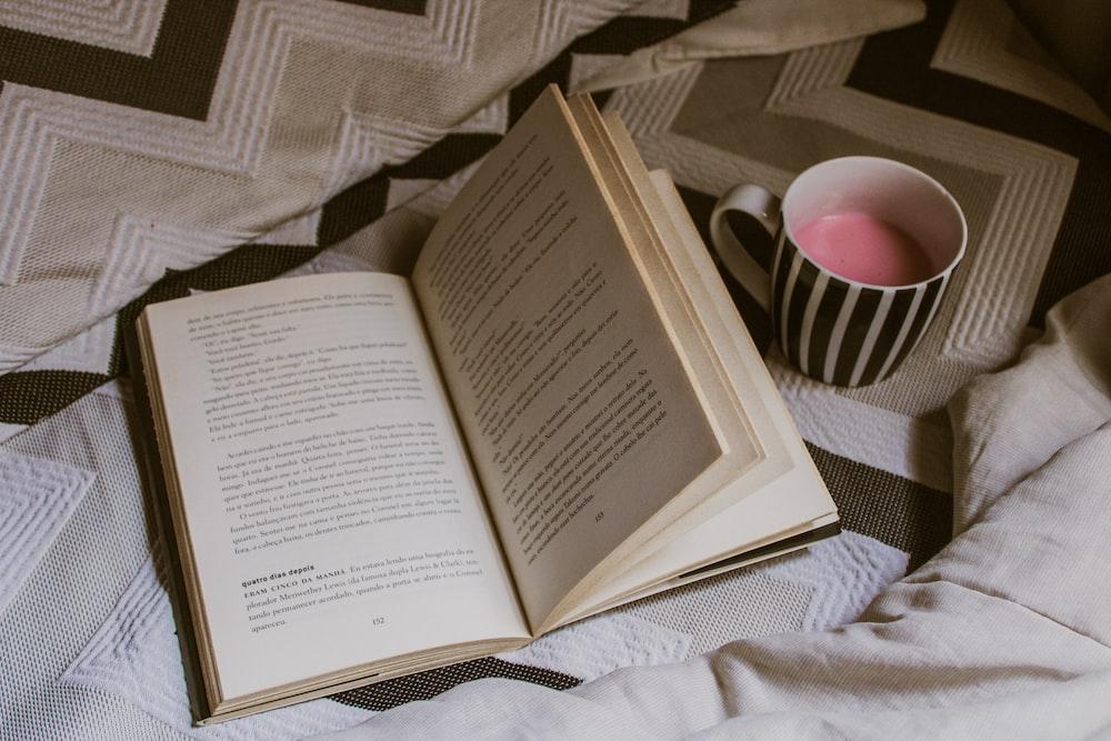 opened white book beside white and black ceramic mug