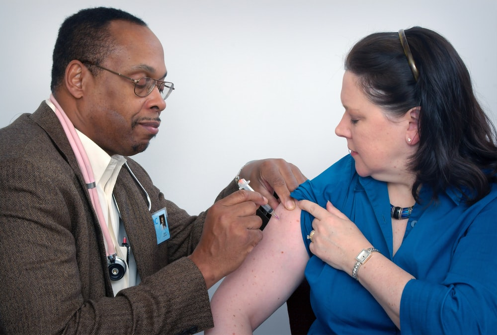 man inject woman on right arm