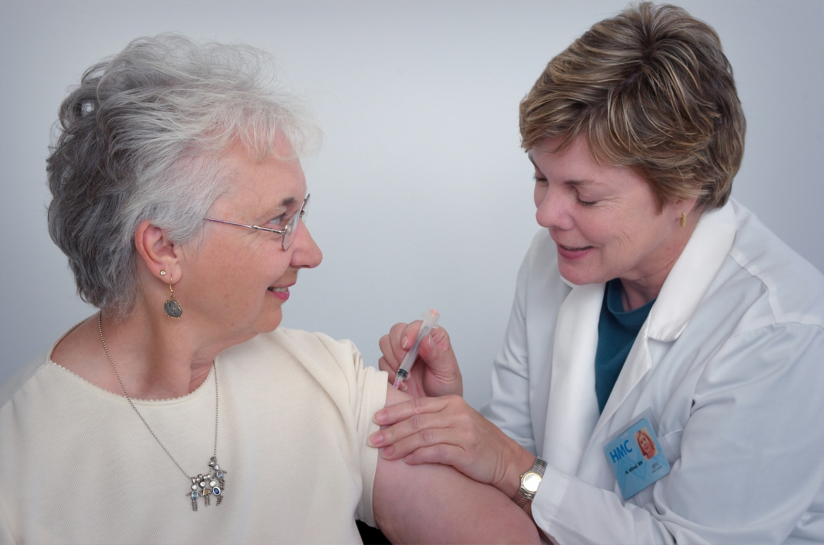 Doctor administering shot to elderly woman