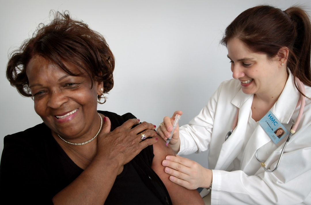 Depicted here, in this 2006 image was a middle-aged woman, who was in the process of receiving an intramuscular injection from a qualified nurse. The nurse had chosen the woman's left shoulder muscle as the injection site, and was using her left hand to stabilize the area.