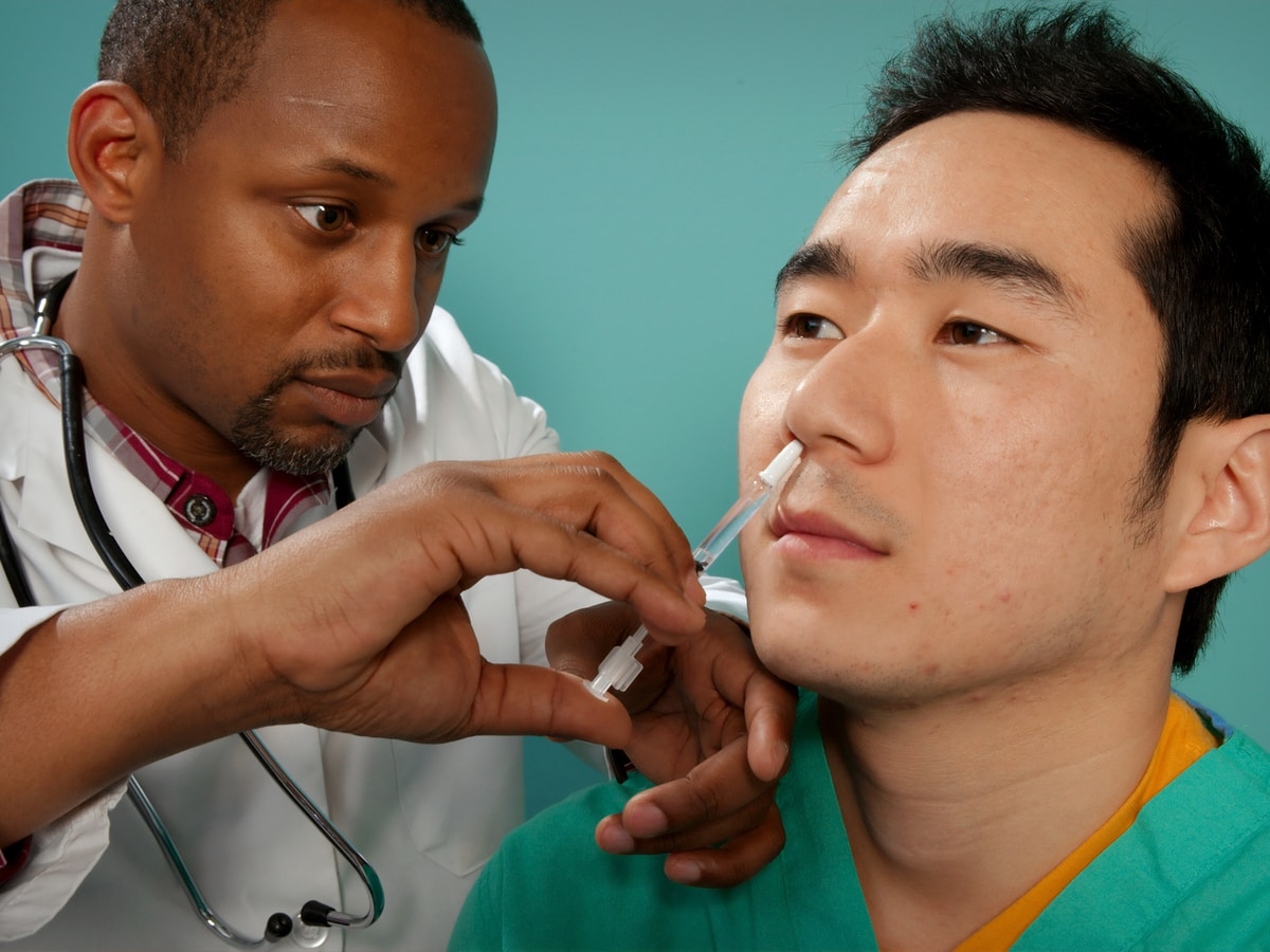 vacuna intranasal, doctor suctioning on man's nose