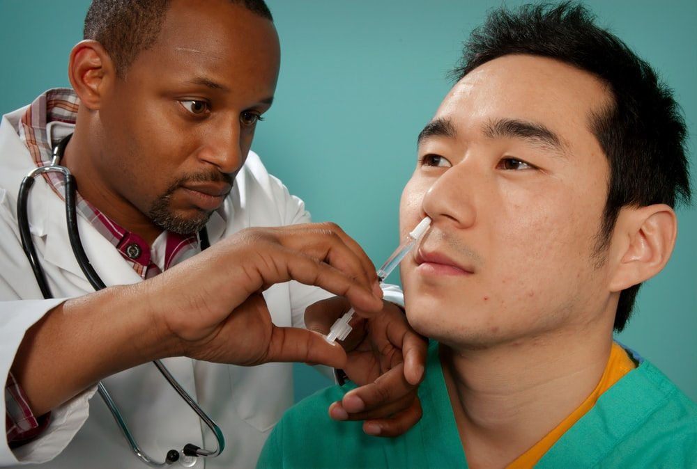 doctor suctioning on man's nose