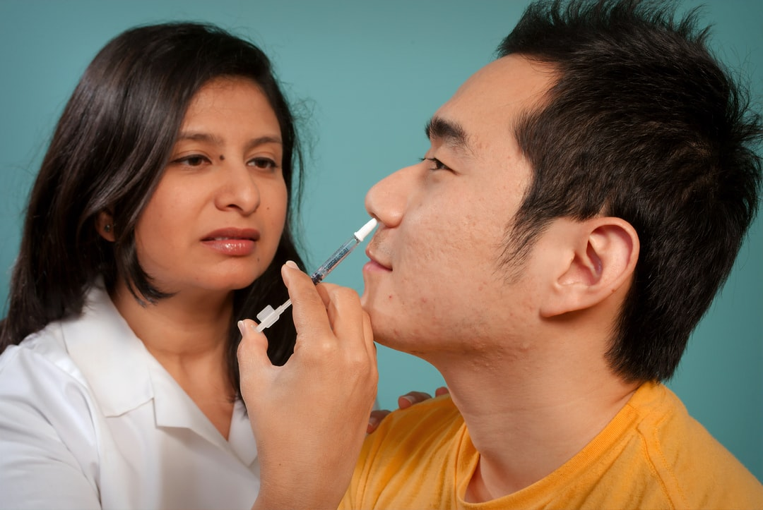 This 2009 image depicts a healthcare practitioner as she was administering the H1N1 live attenuated intranasal vaccine (LAIV) to an Asian man. Using a small syringe, she was delivering the vaccine mist into the man's left nostril.