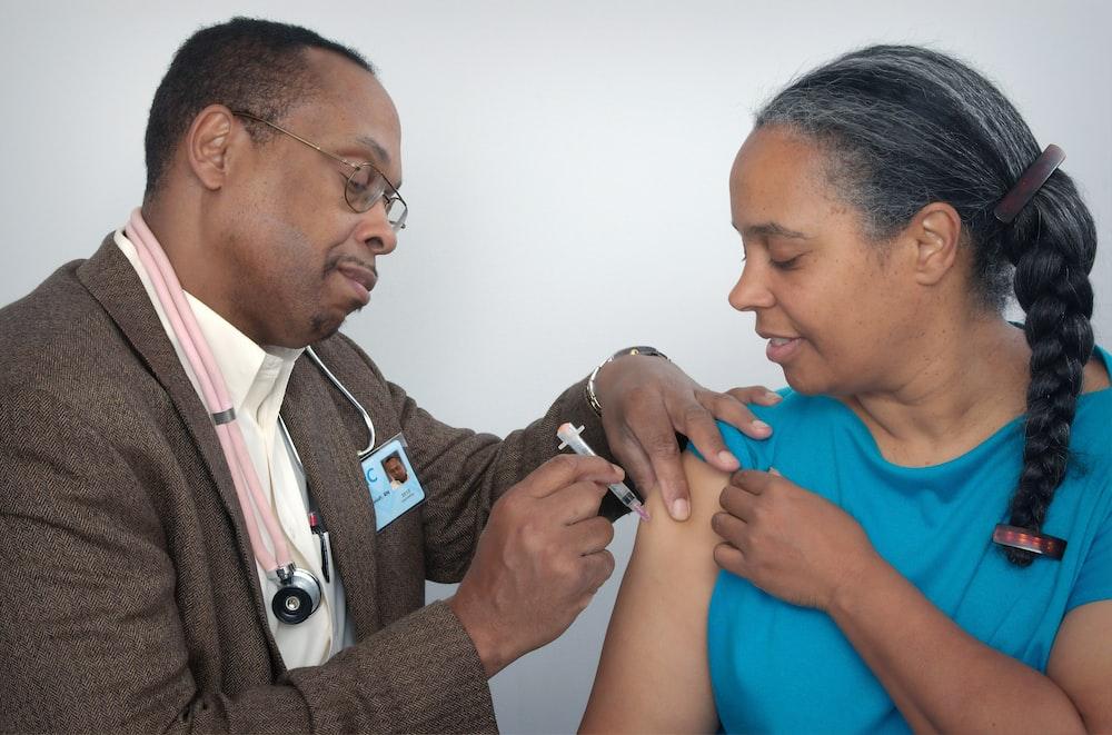man doing syringe on woman wearing blue shirt