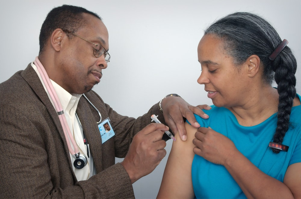 man doing syringe on woman wearing blue shirt