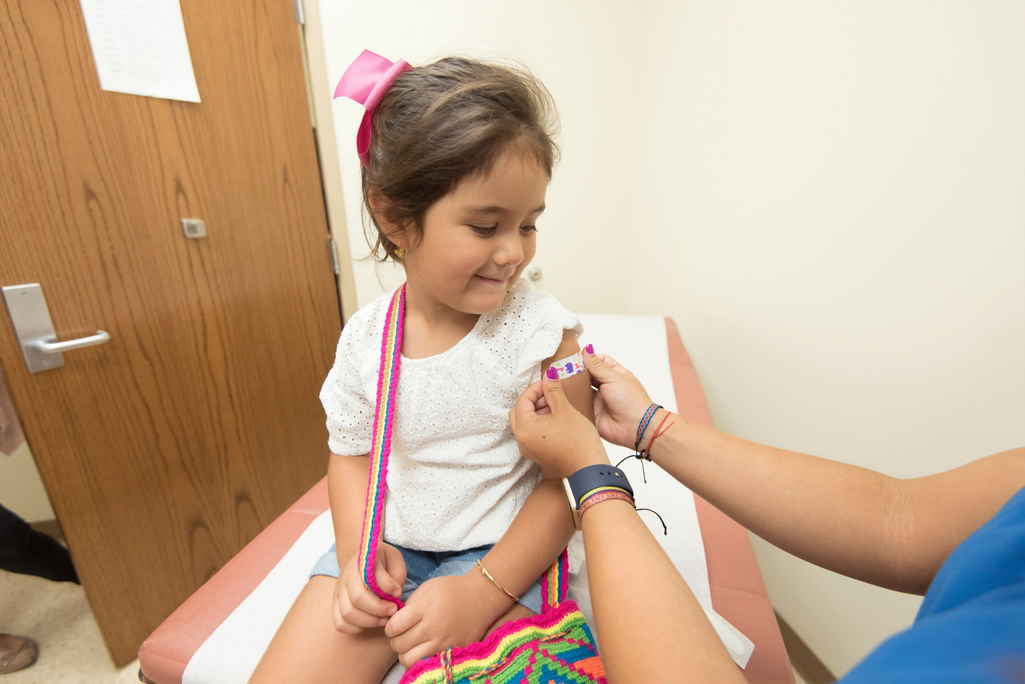 In this 2017 photo, captured inside a clinical setting, a health care provider was placing a bandage on the injection site of a child, who had just received a seasonal influenza vaccine. Children younger than 5-years-old, and especially those younger than 2-years-old, are at high risk of developing serious flu-related complications. A flu vaccine offers the best defense against flu, and its potentially serious consequences, and can also reduce the spread of flu to others.