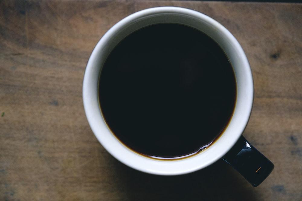 white and black ceramic mug filled with black liquid