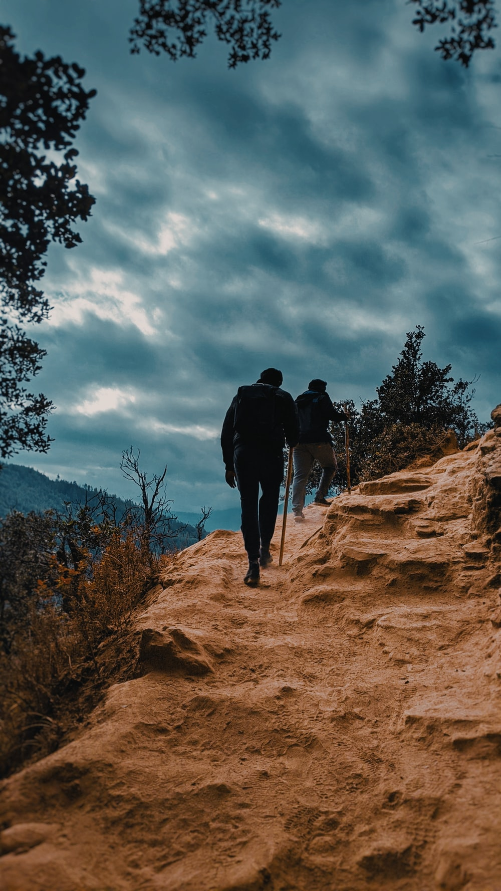 two men hiking on rocky field during day