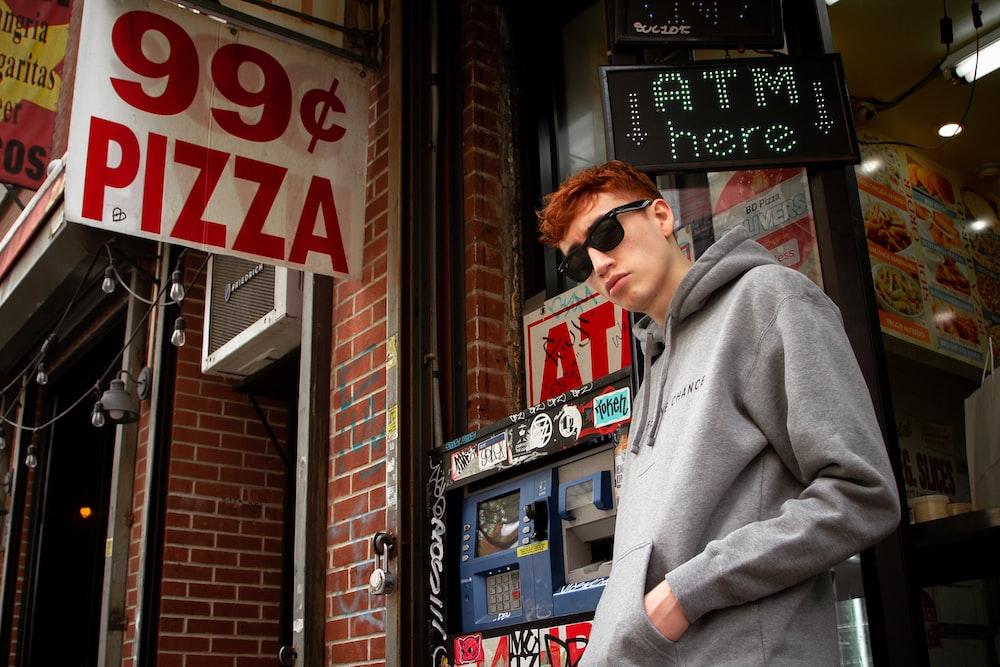 man wearing black sunglasses beside building