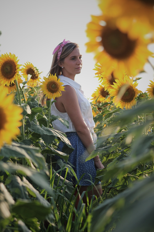 woman standing in between sunflowers