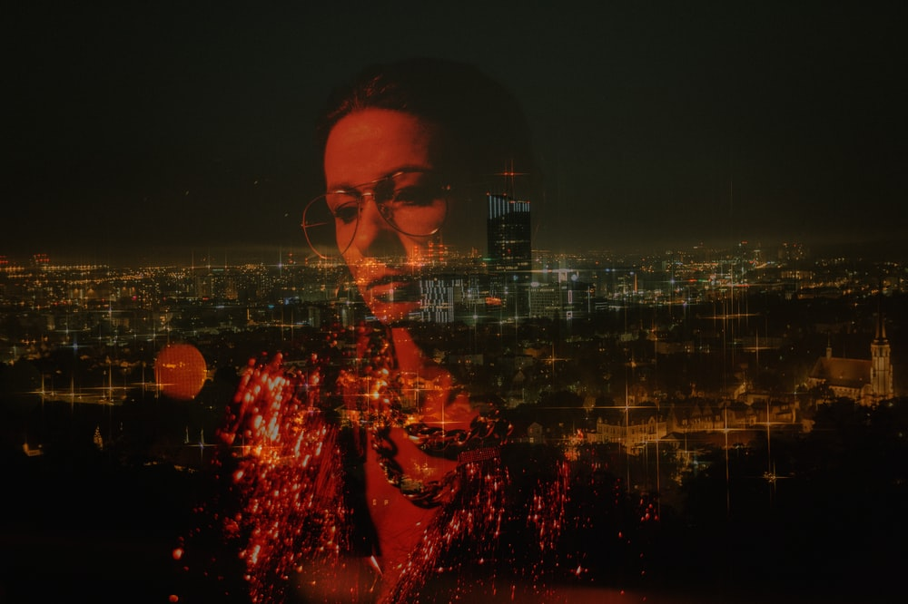 woman reflection on glass overlooking city at night