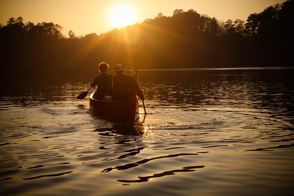 men rowing boat during sunset