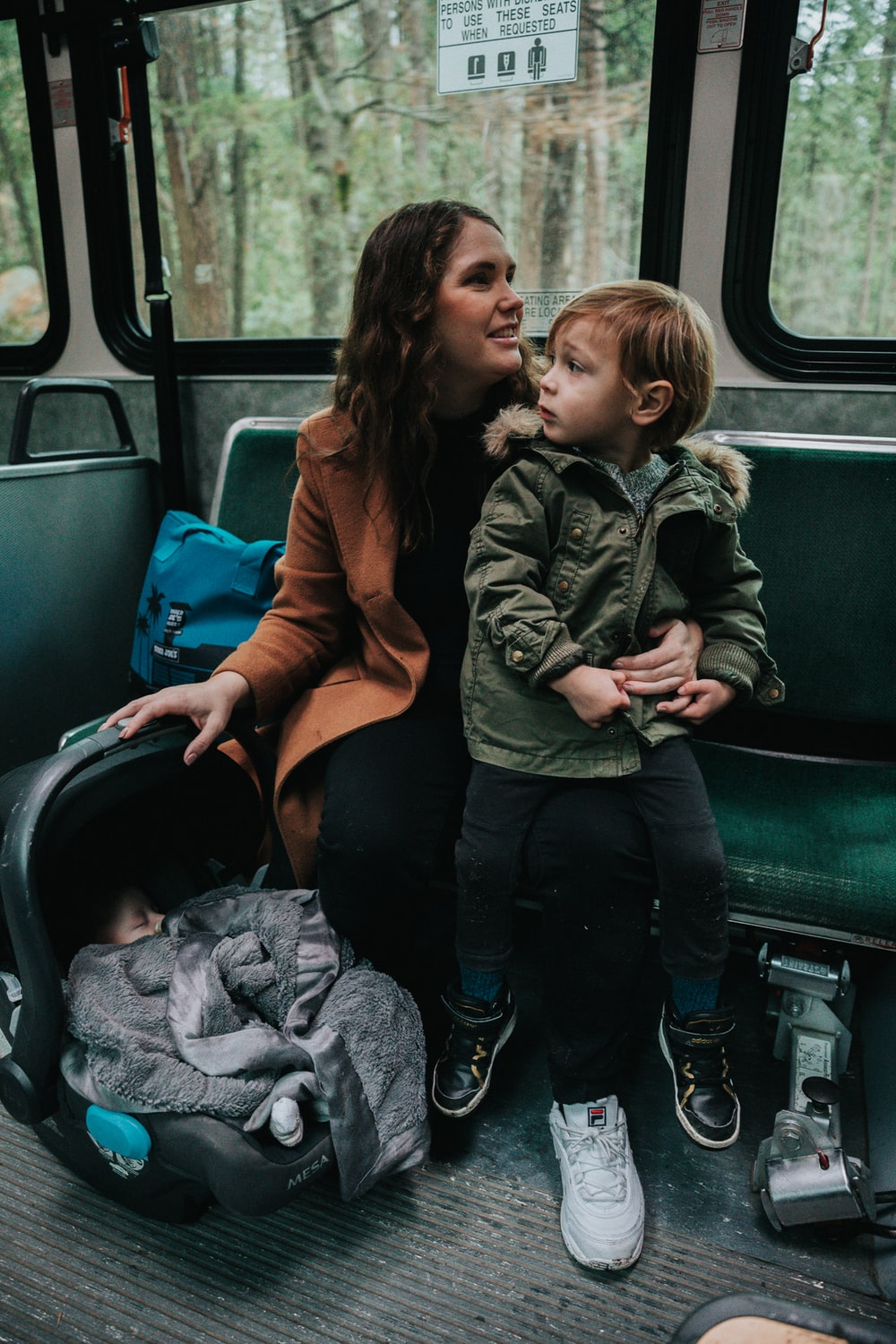 shallow focus photo of boy sitting on woman's lap