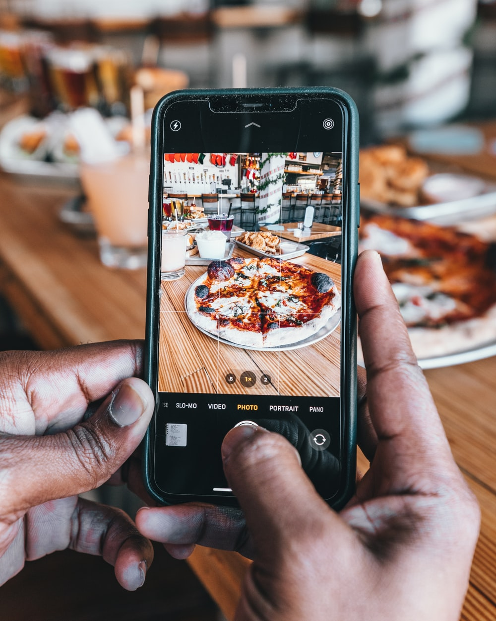 person taking photo of pizza