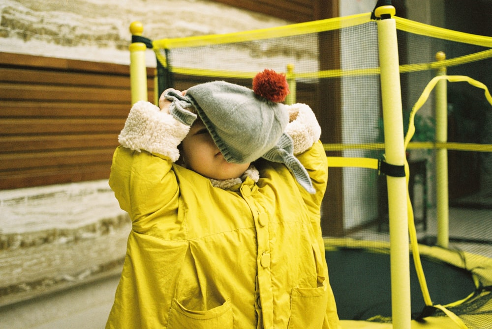 baby wearing yellow jacket and gray bennies