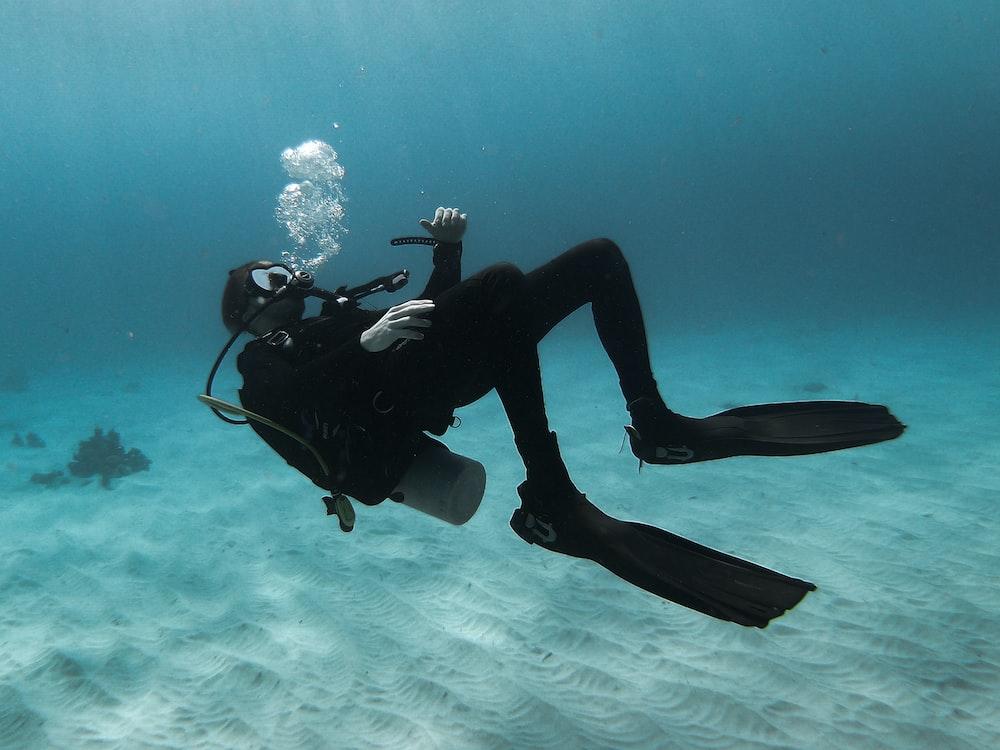 man in scuba diving suit in water