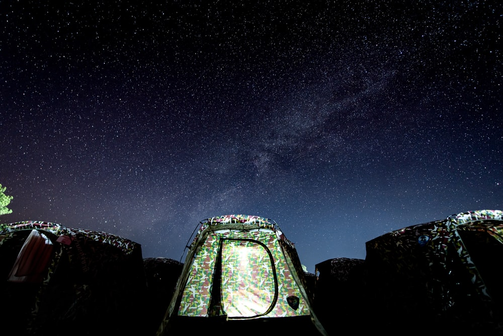 green dome tent under a starry night sky