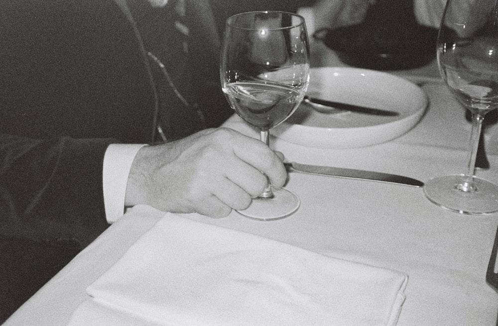 man touching near empty wineglass