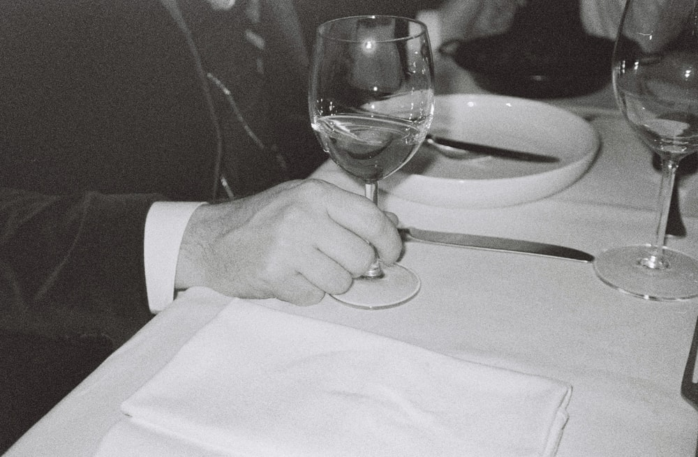 man touching near empty wineglass