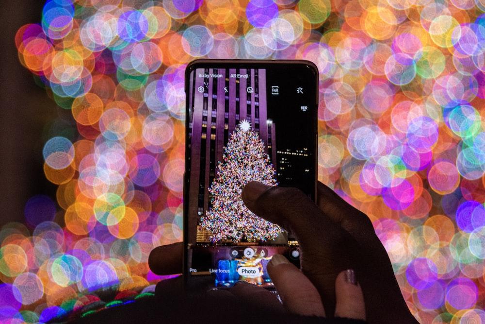 shallow focus photo of taking photo using smartphone