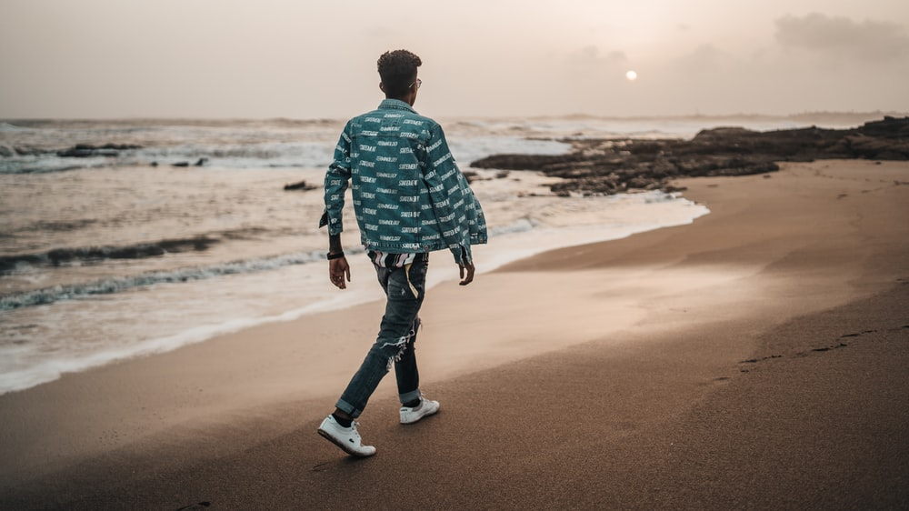 man walking along the seashore during daytime