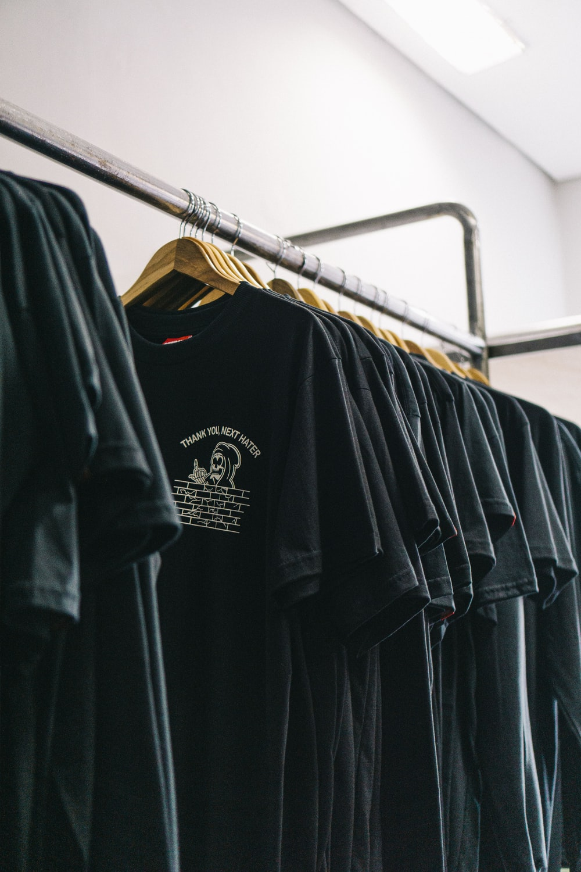 hanged black t-shirts beside wall