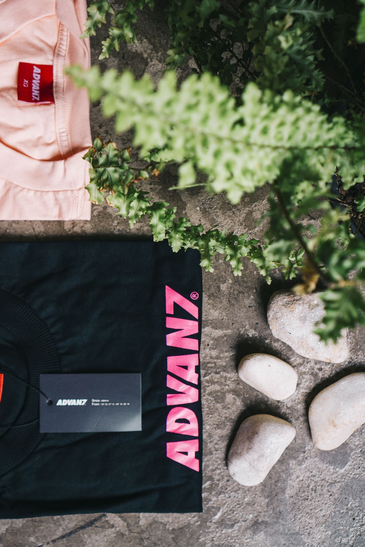 folded black Advanz shirt beside stones
