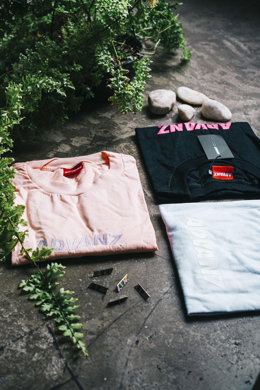three pink, black, and blue shirts