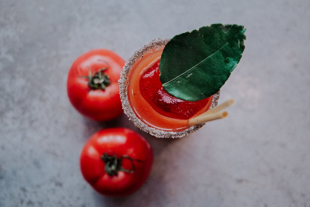 two red tomatoes beside tomato juice cup