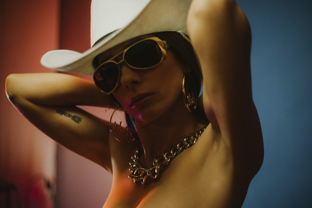 woman wearing white cowboy hat and gold-colored sunglasses