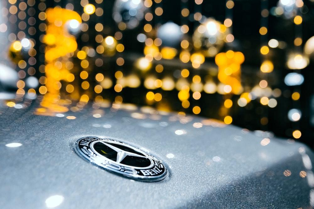 selective focus photography of Mercedes-Benz emblem
