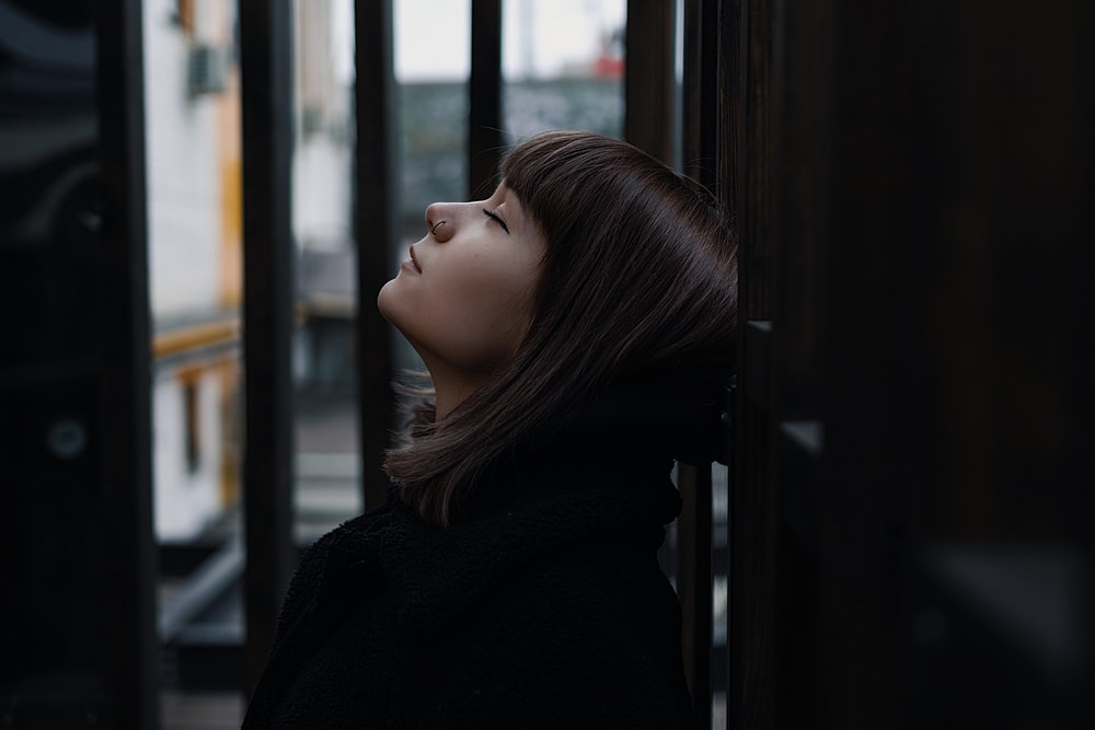 selective focus photography of woman lifting head up with eyes close