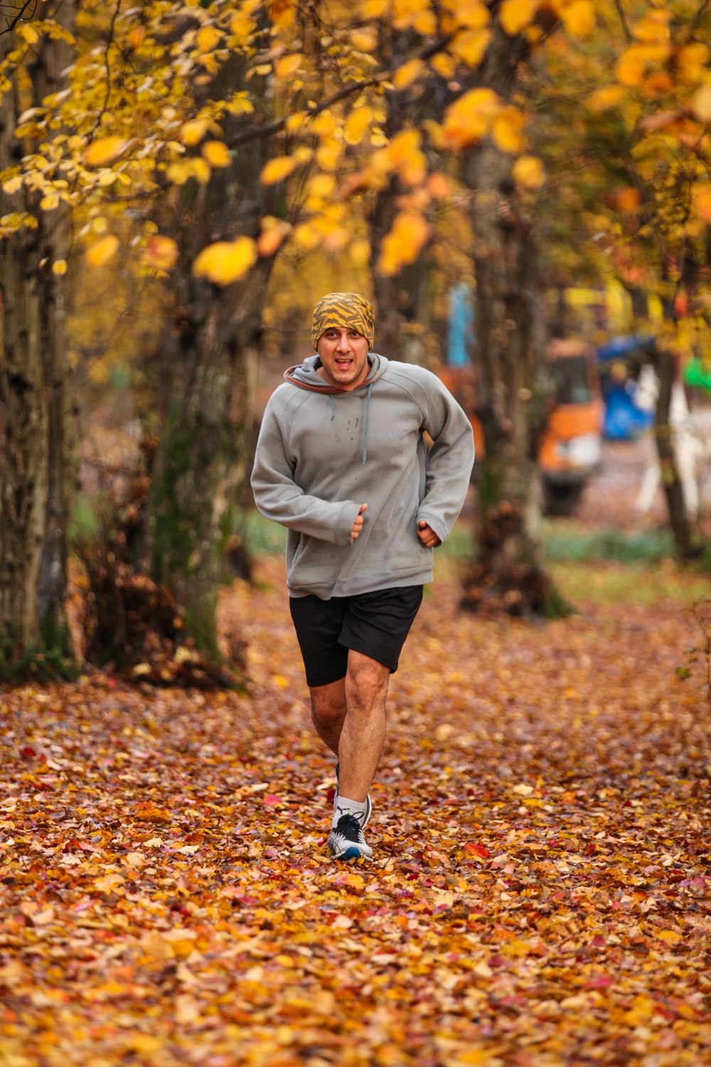 man running on leaf covered field during day