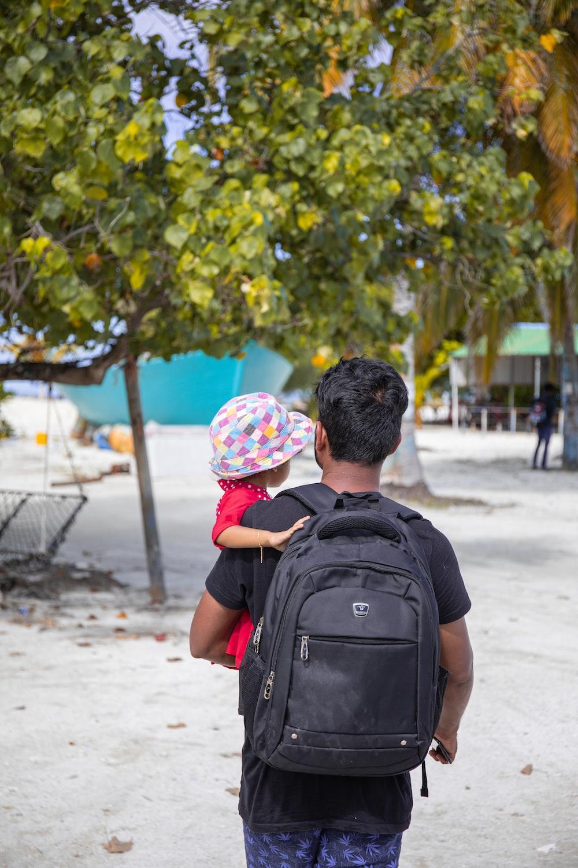 walking man holding toddler during daytime