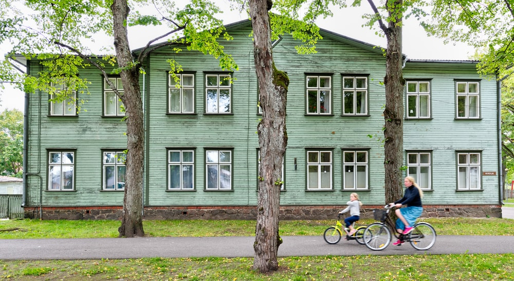 two cycling people passing gray wooden house