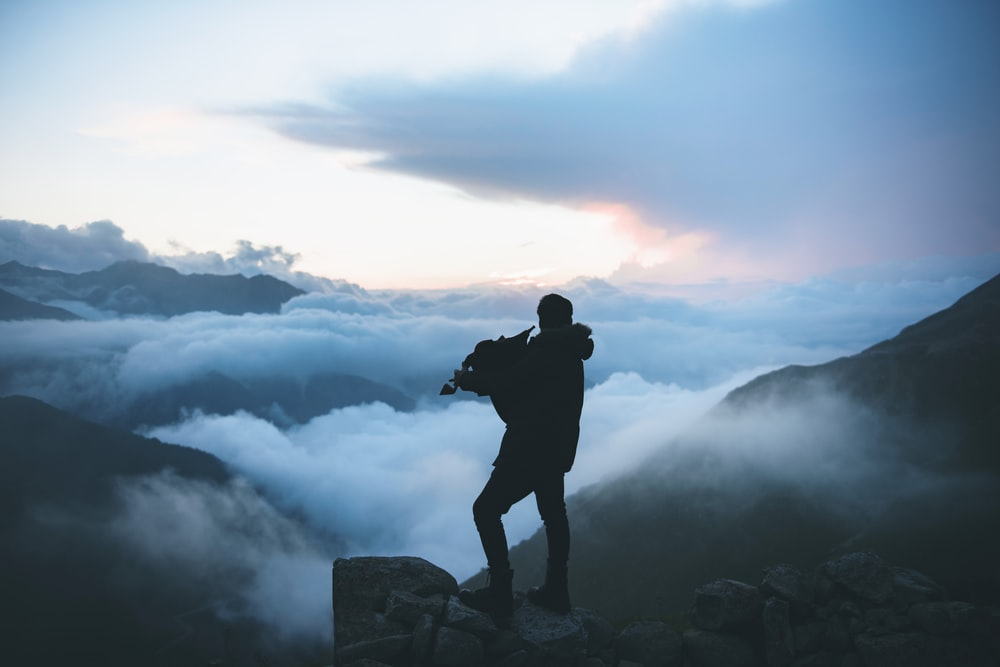 man standing near cliff overlooking clouds
