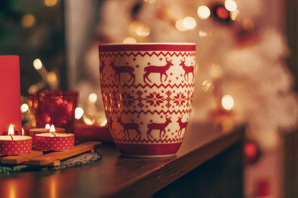 white and red deer print ceramic cup on wooden table